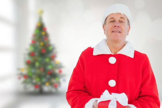 Festive man holding gift against blurry christmas tree in room
