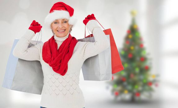 Festive woman holding shopping bags against blurry christmas tree in room