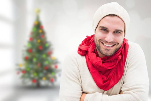 Handsome hipster against blurry christmas tree in room