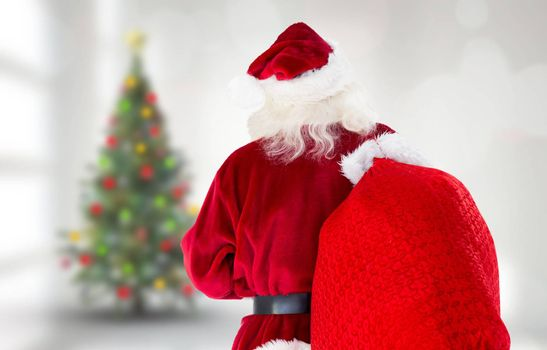 Santa claus carrying sack against blurry christmas tree in room