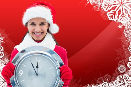 Festive brunette holding clock against christmas themed snow flake frame