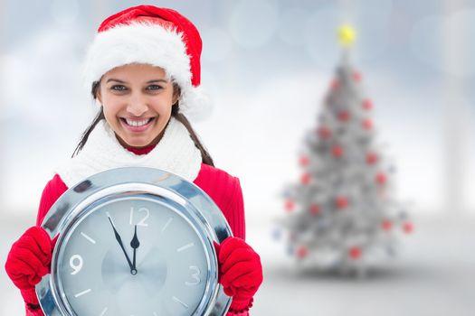 Festive brunette holding clock against blurry christmas tree in room