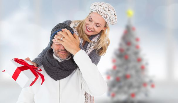 Happy winter couple with gift against blurry christmas tree in room