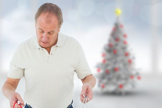 Man looking in shopping bags against blurry christmas tree in room