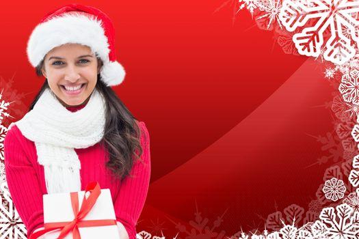 Festive brunette holding gift against christmas themed snow flake frame