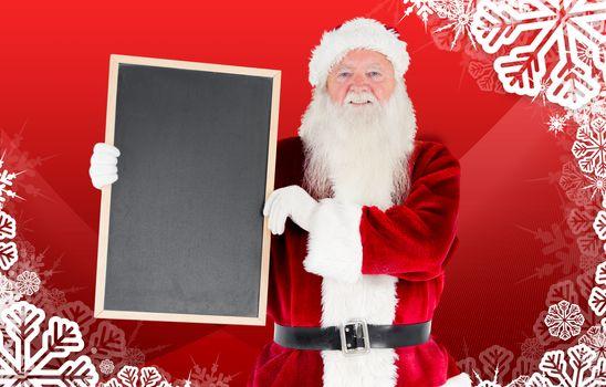 Santa claus showing blackboard against christmas themed snow flake frame