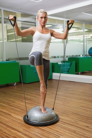 Full length portrait of a young woman doing fitness exercise in fitness studio