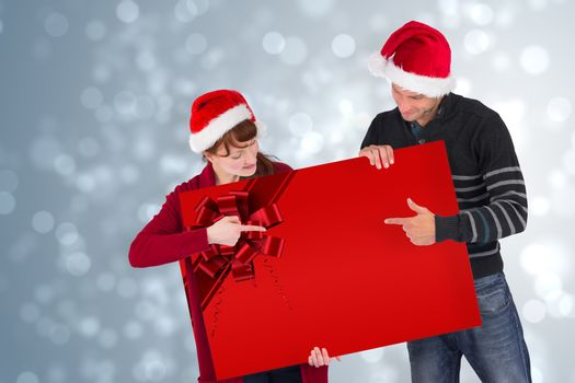 Couple holding a sign with red christmas ribbon