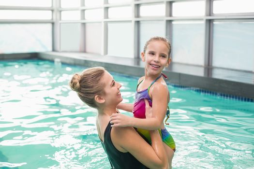 Cute little girl learning to swim with mum