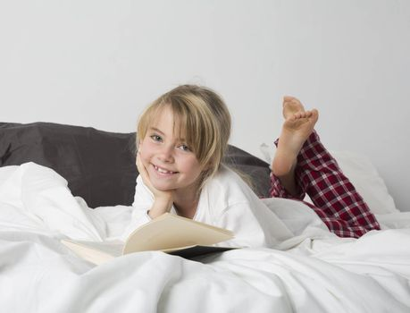 Smiling Young Girl Reading a Book in bed