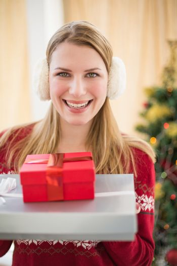 Smiling blonde wearing earmuffs while holding gifts