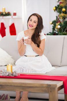 Smiling brunette enjoying a hot beverage at christmas