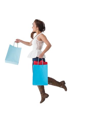 Happy brunette leaping with shopping bags