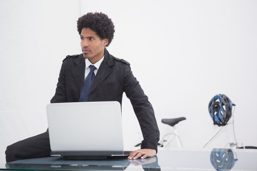 Thoughtful businessman in trench coat using laptop