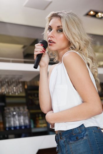 Pretty blonde woman holding a micro while singing