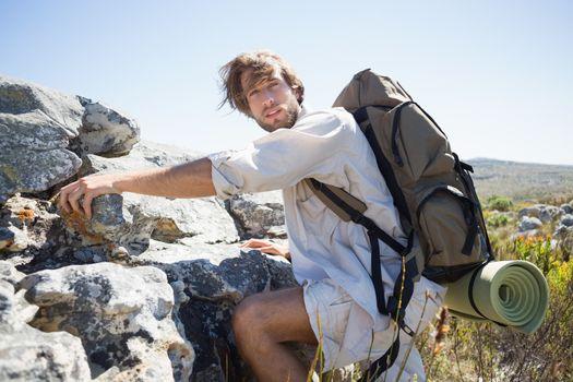 Handsome hiker hiking through rough terrain