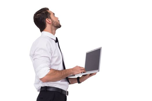Sophisticated businessman standing using a laptop