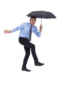 Anxious businessman under umbrella balancing