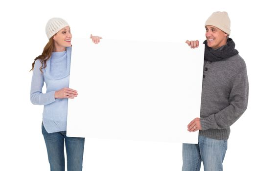 Casual couple in warm clothing holding poster