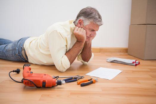 Man lying on floor reading tool instructions