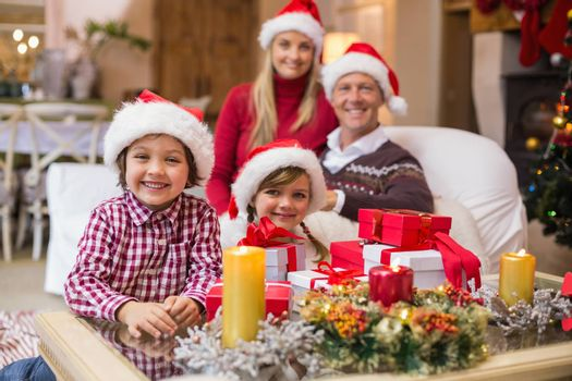 Portrait of a festive family in santa hat at home in the living room