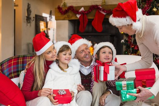 Grandmother giving several gifts to her family at home in the living room