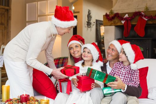 Grandmother giving gift to her family at home in the living room