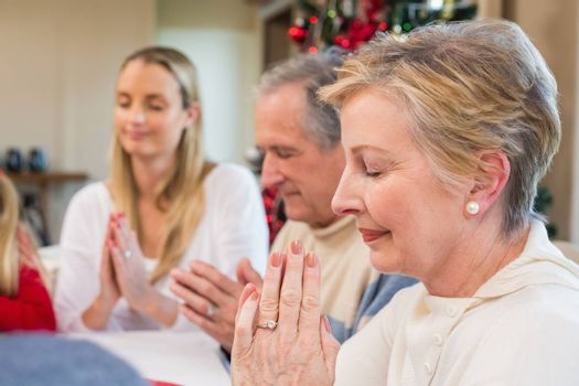 Extended family saying grace before christmas dinner at home in the dining room