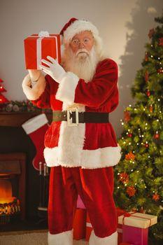 Father christmas holding gift at christmas eve