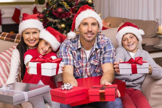 Festive family on the couch offering gifts at home in the living room