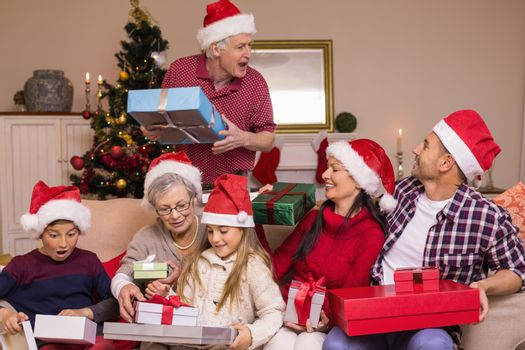 Grandfather giving gift to his family at home in the living room
