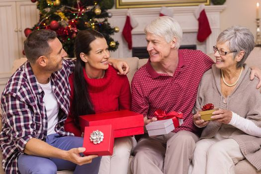 Smiling family holding present on sofa at home in the living room