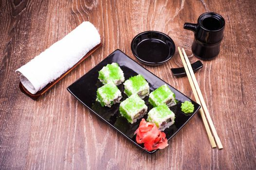 sushi roll set in green caviar with ginger, soy sauce, towel and chopsticks on wooden background