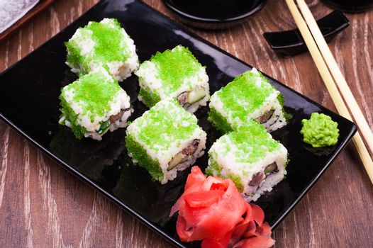 sushi roll set in green caviar with ginger and chopsticks on wooden background