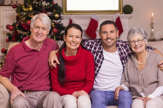Portrait of a happy family sitting on sofa at home in the living room