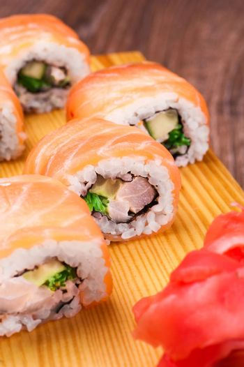 sushi roll set covered in salmon on wooden background