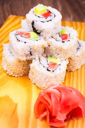 inside out sushi roll with salmon and avocado on wooden background