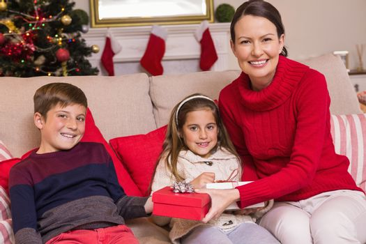 Mother offering gift to her son and daughter at home in the living room