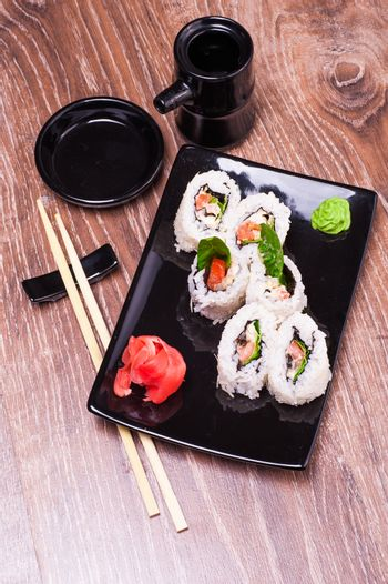 spicy sushi roll set   with ginger, soy sauce, towel and chopsticks n wooden background