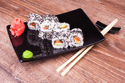 salmon and avocado sushi roll on wooden background