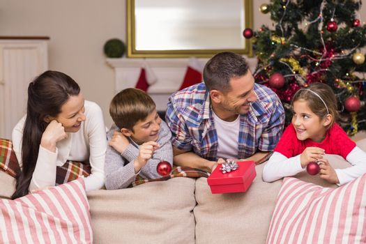 Smiling family leaning on the couch at home in the living room