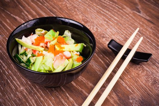 asian seafood and avocado salad on wooden background
