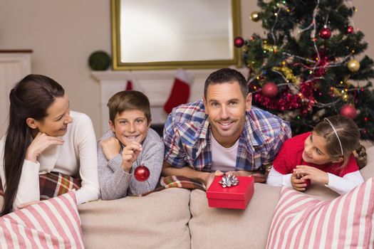 Happy family leaning on the couch at home in the living room