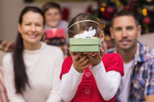 Daughter showing a gift with her family behind at home in the living room