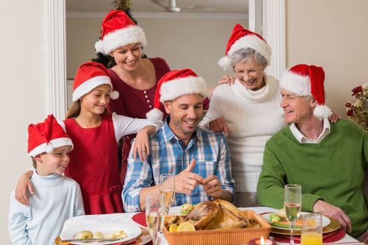 Happy extended family in santa hat at christmas dinner at home in the living room