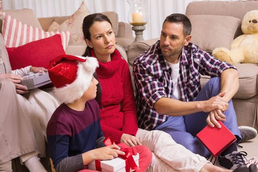 Thinking family sitting and holding gifts at home in the living room