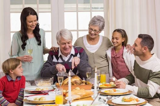 Grandfather carving chicken and his family looking him