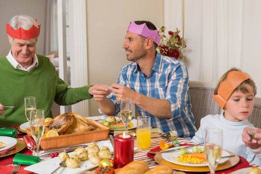 Family reading paper in party hat at home in the living room
