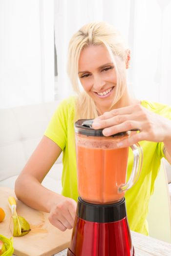 A beautiful mature woman preparing a smoothie or juice with fruits in the kitchen.