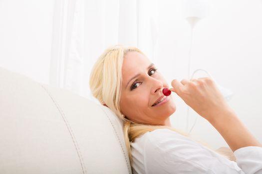 A mature woman enjoying cherries on the sofa.